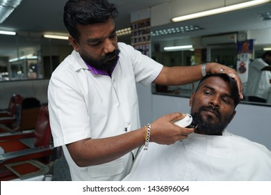 Selangor, Malaysia - 22ND JUNE 2019; An Indian barber cutting hair of male client using machine hair clippers. Hairstylist serving customer at the barbershop.