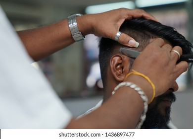 Selangor, Malaysia - 22ND JUNE 2019; An Indian barber shaving hair of male client using sharp razor. Hairstylist serving customer at the barbershop.