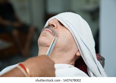 Selangor, Malaysia - 22ND JUNE 2019; Close-up shot an Indian barber cutting mustache of male client using sharp scissors. Hairstylist serving customer at the barbershop.