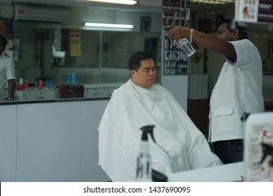 Selangor, Malaysia - 22ND JUNE 2019; An Indian barber spray water to make the head of male client wet before doing a haircut. Hairstylist serving client at barber shop.