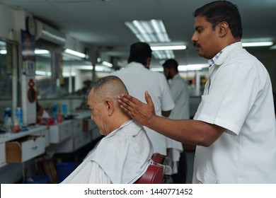 Selangor, Malaysia - 22ND JUNE 2019; An Indian barber give a massage to male client. Hairstylist serving customer at the barbershop.