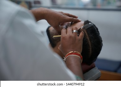 Selangor, Malaysia - 22ND JUNE 2019; Close-up shot, an Indian barber shaving beard of male client using sharp razor. Hairstylist serving customer at the barbershop.