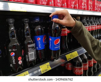 Selangor, Malaysia - 23 June 2019 : View a hand are buying plastic bottle Pepsi carbonated soft drink in a supermarket with selective focus.Pepsi is produced and manufactured by PepsiCo.
