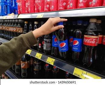Selangor, Malaysia - 23 June 2019 : Young girl hands are buying plastic bottle Pepsi soda soft drink in a supermarket with selective focus.Pepsi is produced and manufactured by PepsiCo.