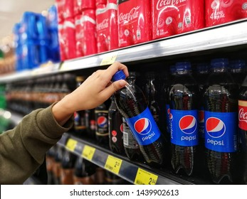 Selangor, Malaysia - 23 June 2019 : Young girl hands are buying plastic bottle Pepsi carbonated soft drink in a supermarket with selective focus.Pepsi is produced and manufactured by PepsiCo.