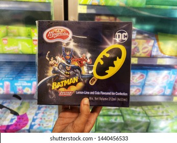 Selangor, Malaysia - 23 June 2019 : Hand hold a packet ice-cream of F&N Magnolia Justice League Lemon-lime and Cola Flavoured ice confection for sell in the supermarket with selective focus.