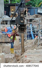 SELANGOR, MALAYSIA â??MARCH 25, 2015: Sheet pile cofferdam driven machine at the construction site. The machine drove the sheet pile to the earth using vibrated hydraulic arm. Workers control.