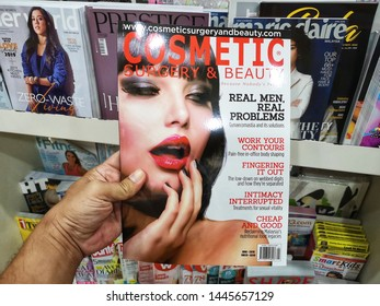 Selangor, Malaysia - 5 July 2019 : Hand hold a COSMETIC Magazine in the book stores with selective focus.
