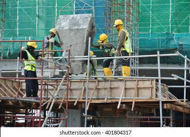 SELANGOR, MALAYSIA â?? DECEMBER 12, 2015: A group of construction workers pouring wet concrete using concrete bucket into the timber form work at the construction site.