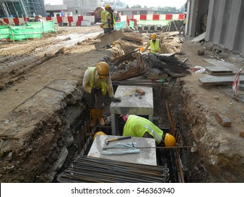 SELANGOR, MALAYSIA -DECEMBER 15, 2016: Construction workers install precast concrete box culvert drain at the construction site. It is used to channel storm water to the nearest monsoon drain.
