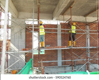 SELANGOR, MALAYSIA -JANUARY 15, 2017: Bricklayer lays clay bricks  to form building walls at the construction site.