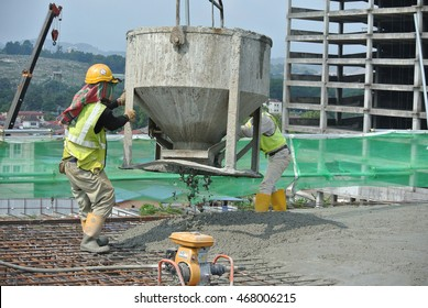 SELANGOR, MALAYSIA -JULY 13,2016: A group of construction workers pouring raw concrete using concrete bucket into the floor slab form work at the construction site.