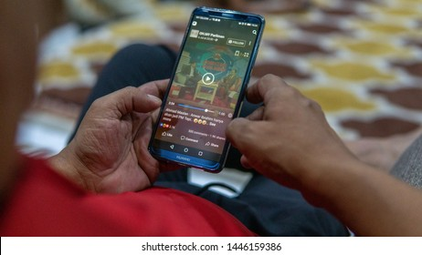 Selangor, Malaysia - July 9, 2019: Watching videos in Facebook apps by using a Huawei smartphone on the hands.