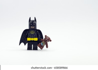 selangor, malaysia. JUNE 04, 2017 lego batman holding teddy bear isolated on white background. Lego minifigures are manufactured by The Lego Group.