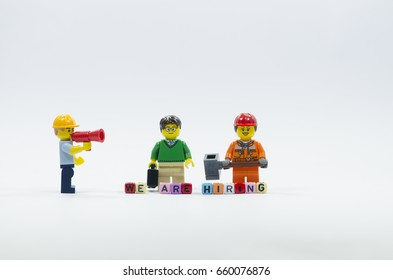 SELANGOR , MALAYSIA. JUNE 13, 2017. Lego worker minifigures standing behind word we are hiring using colorful alphabet beads.