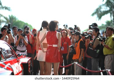 Selangor, Malaysia - June 21, 2009 : Promotional models or Race Queens for the Japan Super GT car racing event walking with photographers surrounding them at Sepang International Circuit