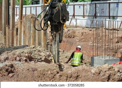 SELANGOR, MALAYSIA � MARCH 12, 2015: Retaining wall sheet pile driving machine at work at construction site. Driven machine driven the pile to the earth using vibrated hydraulic arm. Workers control.