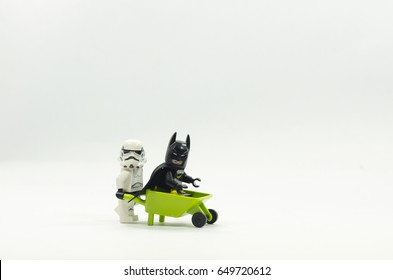 selangor malaysia, MAY 28, 2017. lego batman sitting on wheel barrow while lego stormtroopers pushing the wheel barrow isolated on white background,Lego minifigures are manufactured by The Lego Group.