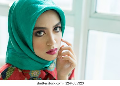 Selangor , Malaysia - Nov 2018 : Portrait of a beautiful asian woman wearing hijab stood by the window, light background.