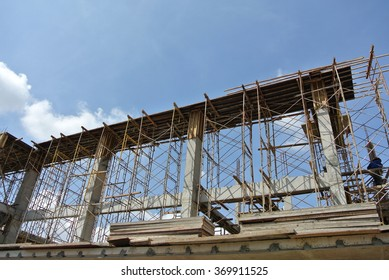SELANGOR, MALAYSIA â?? NOVEMBER 25, 2014: Construction workers fabricating timber beam form work at the construction site. Workers stand on a temporary structure which is supported by scaffolding.