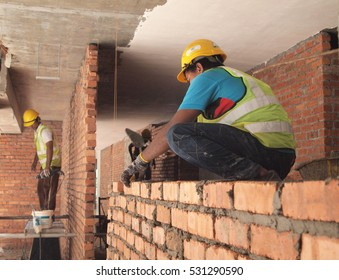 SELANGOR, MALAYSIA -NOVEMBER 25, 2016: Bricklayer worker lay red clay bricks to form building walls at the construction site. Clay bricks bond using cement mortar.