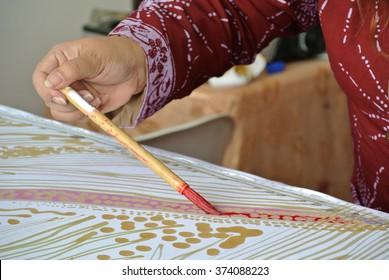 SELANGOR, MALAYSIA â?? SEPTEMBER 06, 2015: A lady doing Malaysian traditional batik tulis using hot wax on piece of white cloth.