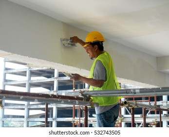 SELANGOR, MALAYSIA -SEPTEMBER 06, 2016: Construction site workers are doing concrete ceiling soffit skim coat work at the construction site. Two layers apply to get the smooth surface.