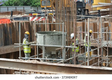 SELANGOR, MALAYSIA â?? SEPTEMBER 15, 2015: A group of construction workers pouring concrete using concrete bucket into the pile cap form work on September 15, 2015.
