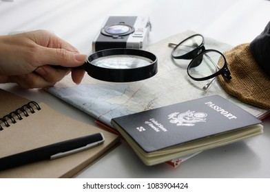 Select destination/Women's Hand Picking a Magnifier - stock imageThe device, a map of the world, America's passport.Camera - photography equipment, glasses, travel equipment, white background closeup