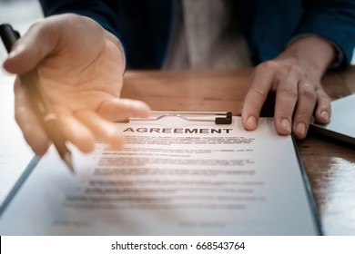 select focus agreement paper,estate agent gives pen and documents agreement with customer to sign contract. Concept agreement
