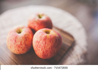 Select focus of  apple fruit on blurry wooden background.