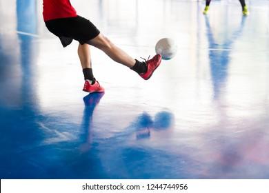 Select focus to futsal player shoot ball to goal. Indoor soccer sports hall. Football futsal player, ball, futsal floor. Sports background. Youth futsal league.