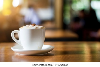 select focus on hot coffee  cappuccino mug on wood table in morning