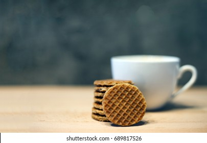 select focus piece of brown homemade stroopwafel snack and ceramic coffee cup on wood table and copy space for text made from daugh and syrup in original tast from dutch