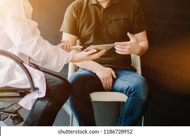select Focus,The doctor is consulting with testicular cancer patients about testicular cancer tumors obtained from the lab so that the patient knows the symptoms and stage of testicular cancer