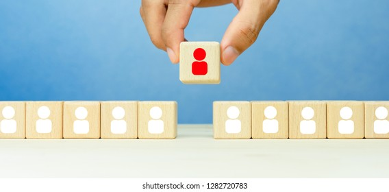 Select good leader or staff and recruitment business, Businessman hand choose wooden blocks with people icons over wooden table