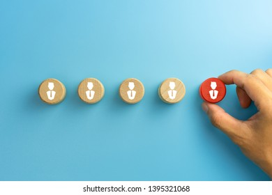 Select team leader, staff, building a good team, human resources and management concepts, Hand holding a wooden blocks with people icon on blue background, copy space