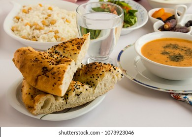 Selected bread of Ramadan (pide) on the iftar table near a glass water and soup.White background,isolated.
