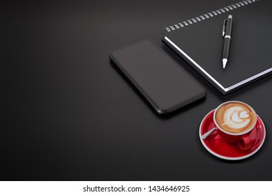 Selected focus black spiral notebook black pen ,smartphone and red cup of coffee on black desk, business office desk minimal style. with copy space for your text or graphic.
