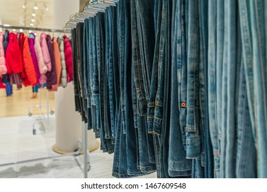 Selected focus close up view at row of jeans or denim trousers and slacks hang on hanger and background of colourful winter jackets for kid inside fashion clothes outlet or second hand store.