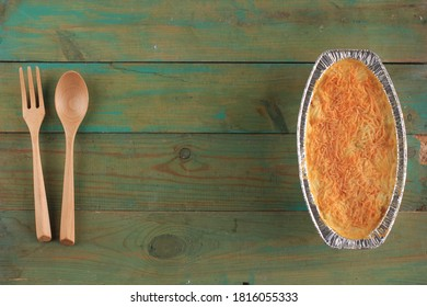 Selected Focus Copy Space Top View  Spaghetti Brulle on Oval Alumunium Foil with Wooden Spoon. Spaghetti Brulee is Baked Spaghetti with Bechamel and Bolognese Sauce
