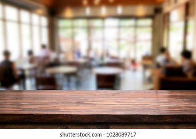 Selected focus empty brown wooden table and Coffee shop or restaurant blur background with bokeh image. for your photomontage or product display