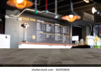 Selected focus empty brown wooden table and Coffee shop blur bac