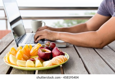 Selected focus fresh fruit on the plate with man working on laptop ocean view