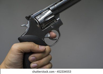 [Selected focus] Left hand holding the gun magnum with a finger on the trigger , Left hand and pistol , Shooting sport. Bullet .357 Magnum or .44 Magnum ,Russian roulette game.