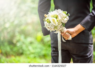 Selected focus on groom holding a white bouquet on back side for his bride on their ceremony.