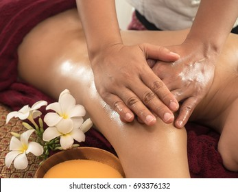 Selected focus on a massager's hand, oil massage on naked women on back with white flower along the body, laying down on the bed.  This massage is for relax, relief muscle pain and stretching