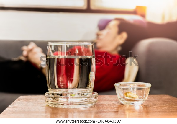 Selected focus on pills with glass of water on table with senior women sleeping on couch