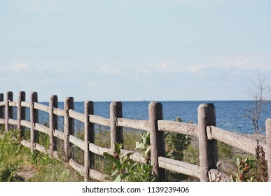 Selected focus on a wooden fence at the Kew Beach Off Leash Dog Park part of Kew-Balmy Beach in Toronto, Ontario.