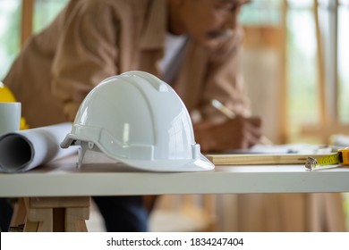 selected focus of safety white hard hat on table work station and blurred background of senior Asian man. home improvement DIY in workshop.